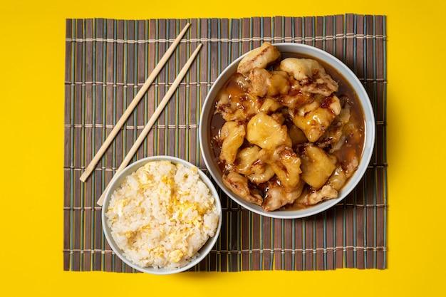 노란색 배경에 밥그릇과 젓가락이 있는 바삭바삭한 튀긴 달콤한 치킨 접시. 중국 음식은 테이크 아웃.