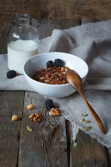 Crunchy honey granola bowl with flax seeds, cranberries and a bottle of milk on a table