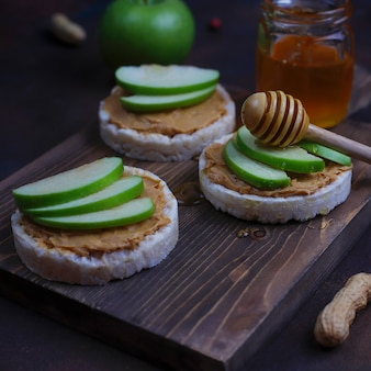 Crunchy natural peanut butter sandwich with rice cake bread and green apple slices and honey.