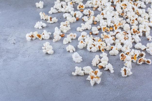 Хрустящий попкорн, разбросанный по мраморной поверхности