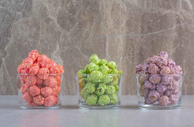 Popcorn croccanti che fuoriescono dall'involucro sul marmo.