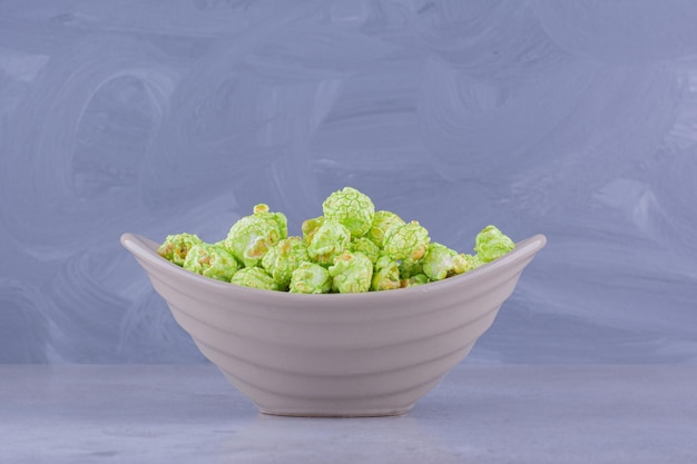 Хрустящая подача конфет попкорна в небольшой миске на мраморном фоне. фото высокого качества