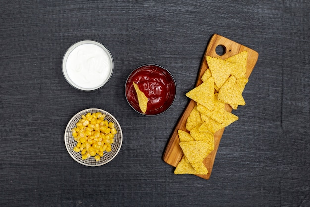 Crunchy traditional nachos with dips and corn