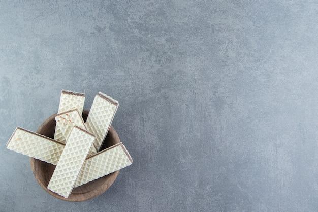 Crunchy vanilla waffles in wooden bowl.