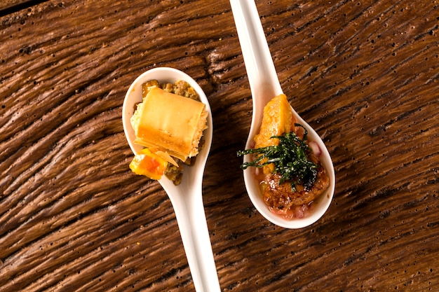 Crunchy with cheese mousse, accompanied with cashew and cashew cashew nuts and pork mignon with creamy canjiquinha and vinaigrette in a spoon. taste gastronomy fingerfood