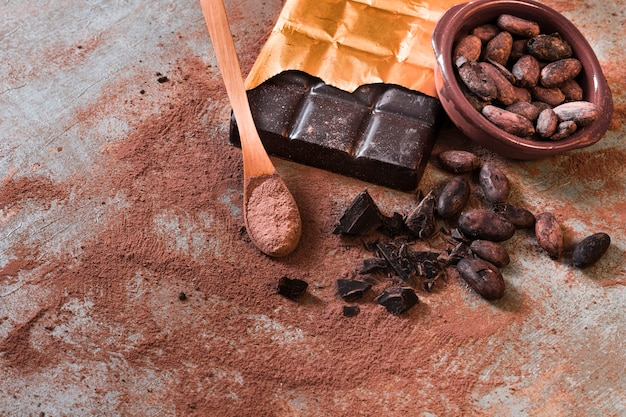Crushed broken chocolate and cocoa beans bowl on rustic backdrop
