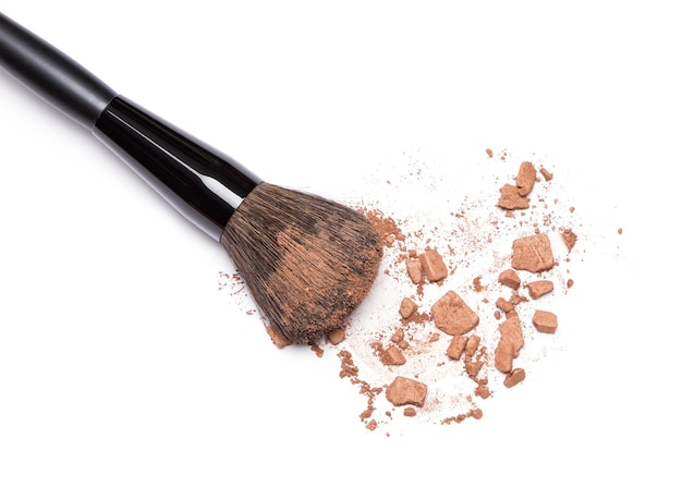 顔の輪郭を描くための白い背景のブロンザーに化粧ブラシで砕いたブロンズパウダー