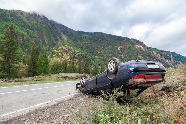 Место аварии разбитого автомобиля на повороте горной дороги