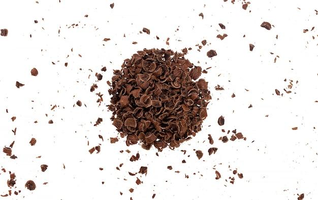 Толченый шоколад. куча молотого шоколада, изолированные на белом фоне с обтравочным контуром, вид сверху
