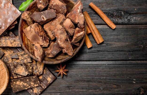 Шоколад толченый с какао-порошком. на деревянном фоне.