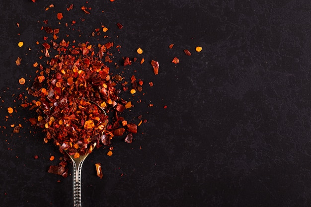 Crushed dried chili peppers in an iron spoon scattered on a black . , copyspace.