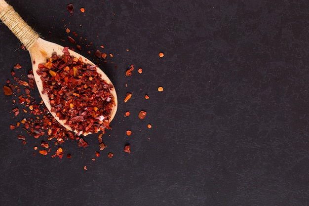 Crushed dried chili peppers in a wooden spoon scattered on a black . , copyspace.