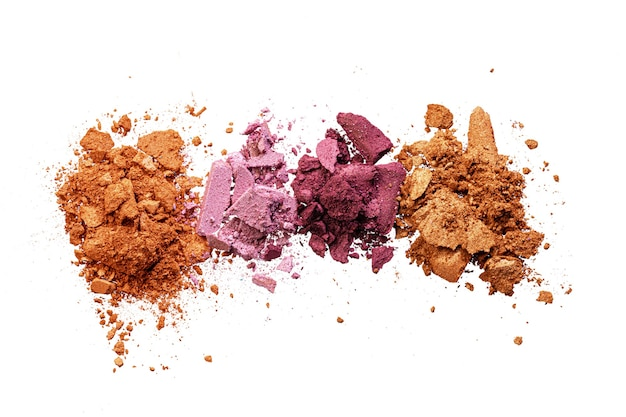 Crushed eyeshadow samples of bright colors isolated on white background