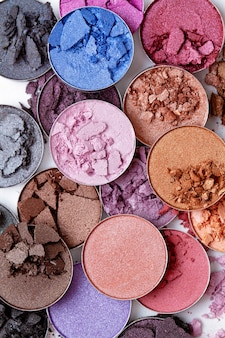 Crushed eyeshadows over the white background. make up artist, beauty salon, beauty blog