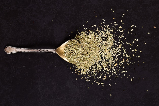 Crushed oregano scattered in an iron spoon on a black table. , copyspace.