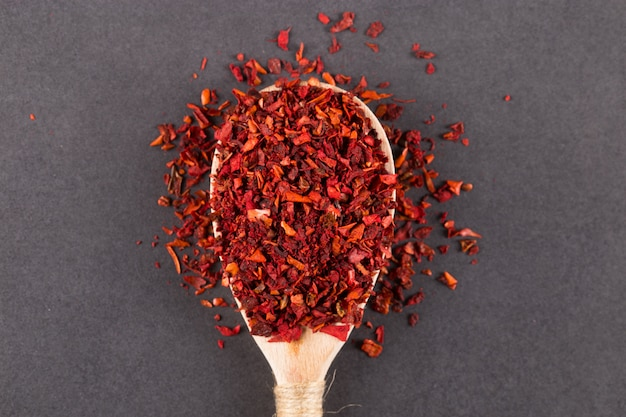 Crushed paprika in a wooden spoon, on a stone table. copyspace.