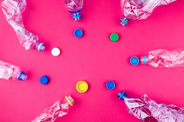 Crushed pet bottles and colorful caps on vivid pink purple background with empty space
