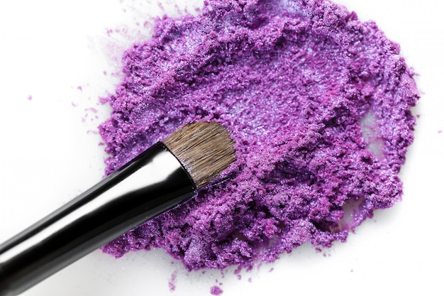 Щебень фиолетовые тени для век и макияж кисти на белом фоне