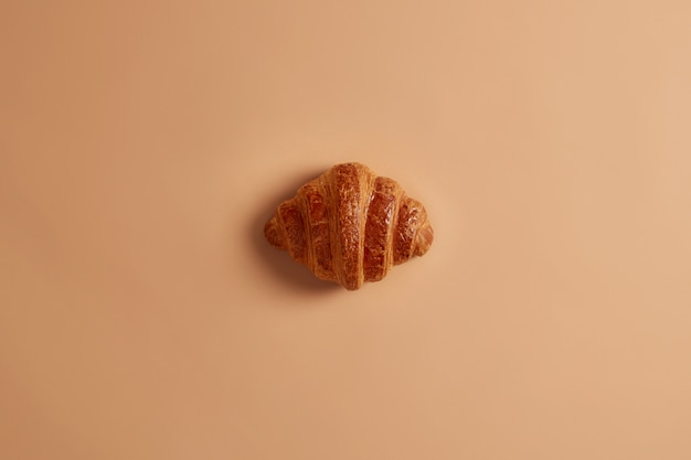 Crust delicious sweet buttery croissant for breakfast on brown background. freshly baked confectionery, yummy dessert, junk food. homemade appetizing bakery product for sweet tooth. french food