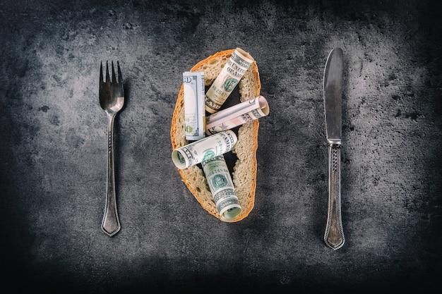 콘크리트 보드에 달러 지폐 포크와 나이프로 가득 찬 빵 껍질. 톤 이미지.