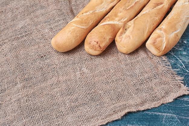 Crusty baguette bread on blue table.
