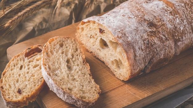 Crusty ciabatta  bread ready to eat. fresh ciabatta bread on wooden cutting board. toned photo
