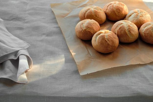 Хрустящие круглые булочки, известные как кайзерские или венские булочки. булочки на бумаге для выпечки на столе с льняной скатертью.
