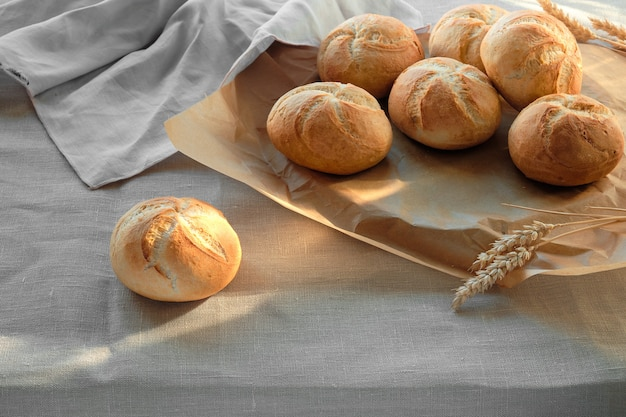 リネンのテーブルクロスで覆われたテーブルの上にカイザーまたはウィーンロールとして知られている無愛想な丸いロールパン。