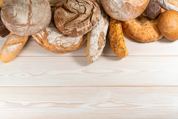 Crusty round bread rolls, known as kaiser or vienna rolls on linen towel on light background, flat lay with copy-space