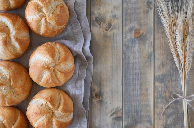 Crusty round bread rolls, known as kaiser or vienna rolls on linen towel on rustic wood