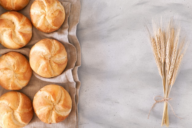 Crusty round bread rolls, known as kaiser or vienna rolls with a bunch of wheat ears on light background