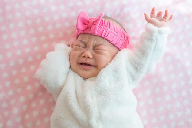 生まれたばかりの赤ちゃんの女の子の叫びは、ベッドにセーターとピンクのヘッドバンドを着用します