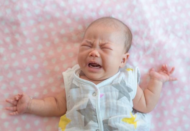 ベッドで生まれたばかりの赤ちゃんの女の子の叫び