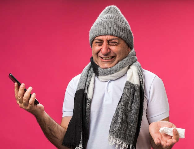 복사 공간이 분홍색 벽에 고립 된 전화와 냅킨을 들고 겨울 모자를 쓰고 목에 스카프와 성인 아픈 백인 남자를 울고