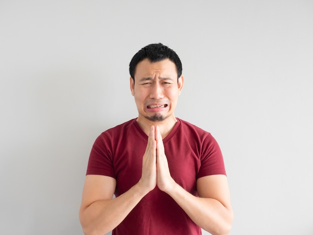 Crying asian man asking for forgiveness or begging the god for good fortune.