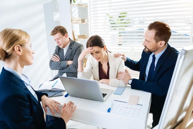 Плачет на работе. напряженная расстроенная коллега плачет, пока ее коллеги успокаивают ее и сидят