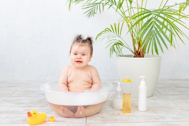 Плачущий ребенок моется в миске с пеной