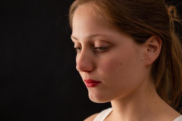 Плачущая блондинка смотрит вниз на темном фоне