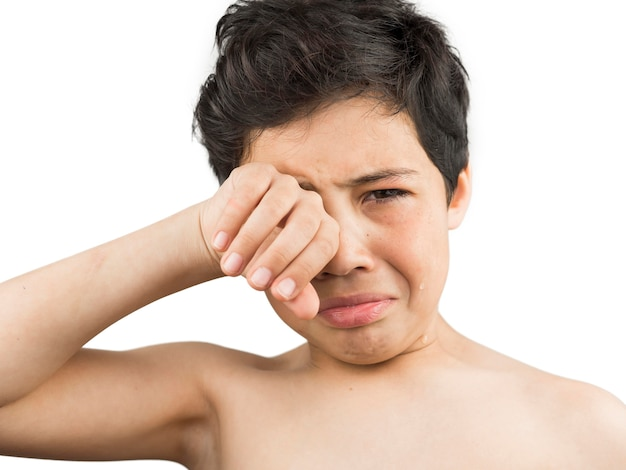 Crying boy covering his tears with hand