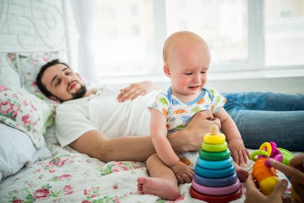 Плачущий мальчик сидит рядом с успокаивающим отцом и игрушками