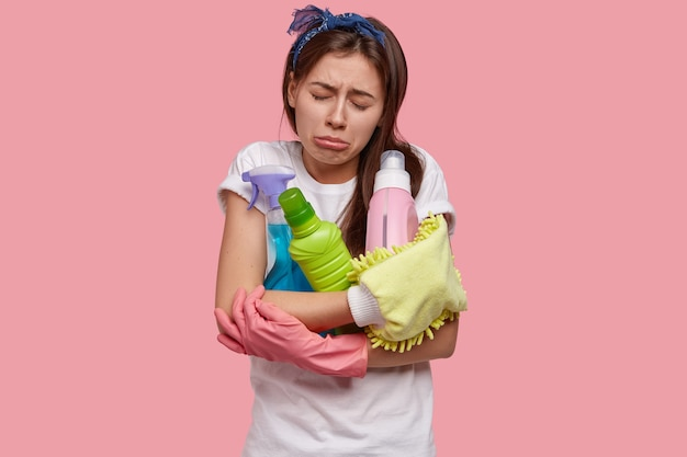 Плачет разочарованная, уставшая молодая женщина недовольна после генеральной уборки, у нее есть все необходимые принадлежности, моющие средства, жалкое выражение лица.