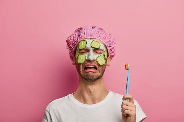 불만족스러운 남자가 울고 칫솔을 들고 오이로 얼굴 점토 마스크를 바르고 미용 치료에 지쳤습니다.