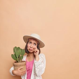 Плачущая грустная азиатская женщина трет глаза вытирает слезы разочарованное выражение лица, сфокусированное наверху, держит горшок с кактусом, чувствуя себя одиноким и расстроенным, одетым в модную одежду, изолированным над бежевой стеной