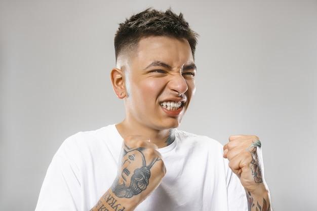 灰色のスタジオの背景で叫んで泣いている感情的な怒っている男。感情的な、若い顔。男性の半身像。人間の感情、表情の概念。