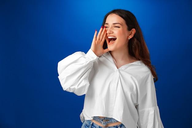 Плачет эмоциональная молодая женщина кричит на синем студийном фоне