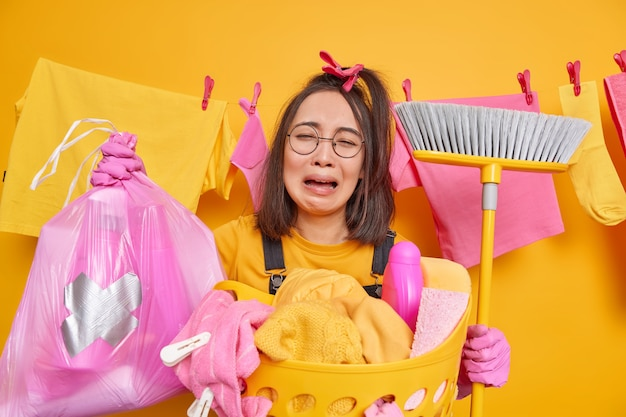 Crying frustrated asian woman holds polythene bag with bottle of detergent broom for sweeping floor has exhausted dejected expression wears round spectacles rubber gloves does laundry at home