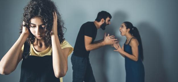 両親と泣いている女の子が家で争う