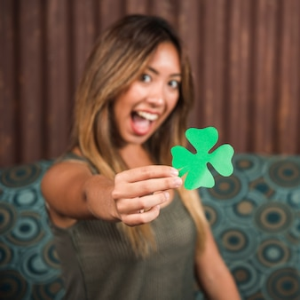 Crying happy woman holding green paper clover