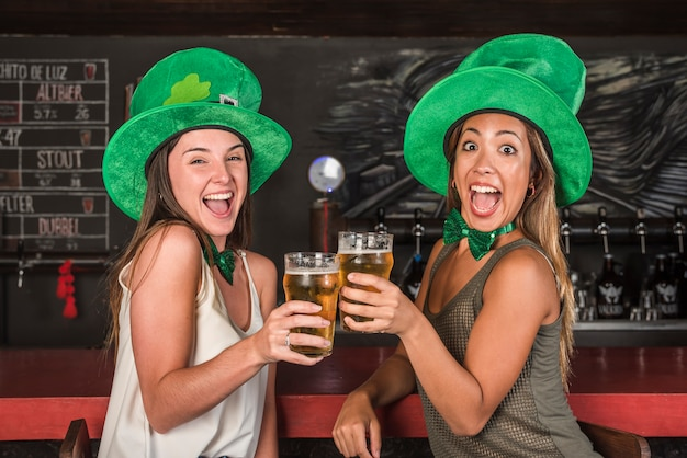 Crying happy women in saint patricks hats clanging glasses of drink at bar counter