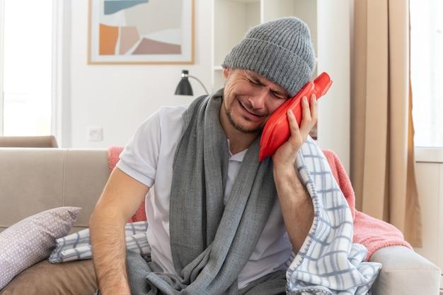 Uomo slavo malato che piange con una sciarpa intorno al collo che indossa un cappello invernale con una borsa dell'acqua calda seduto sul divano in soggiorno couch
